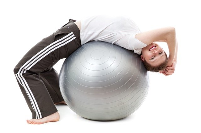 lady adjusting her back using a yoga ball to stretch