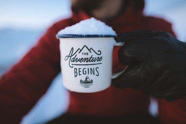 "A mug quoting ""The Adventure Begins"""