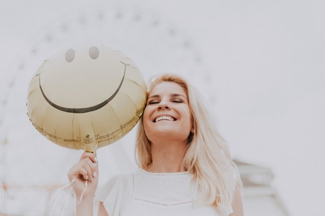 Blonde women smiling holding a smiley face balloon next to her head